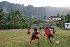 Boys play soccer at the feet of Matebien. This community chose interventions of fish farming and gardening vegetables high in vitamins.