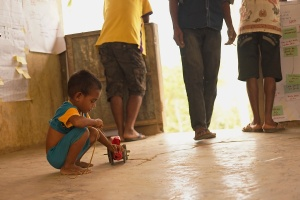A child plays off to the side of the community Action Planning with his home made toy car. Community Action Planning happens in the community. Life in the community does not stop. For two days the meetings become a part of the community. Often while parents and grandparents discuss nutrition issues and solutions children are playing off to the side or even joining in the discussion. The charts in the background are a nutritional calendar, sunshine wheel (reflecting nutritional themes), and a table that people discuss how women and men can take different roles in helping children and new mothers increase their nutrition.